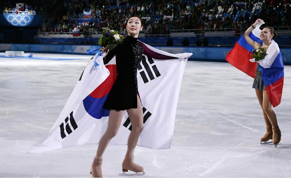Yuna Kim of South Korea, left, and Adelina Sotnikova of Russia skate on the ice following the flower ceremony for the women's free skate figure skating finals at the Iceberg Skating Palace during