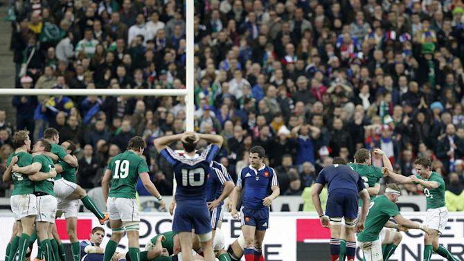 Ireland's rugby team players, in green, celebrate after defeating France and winning the Six Nations Rugby Union tournament at the stade de France stadium, in Saint Denis, outside Paris, Saturday, March 15, 2014. (AP Photo/Christophe Ena)