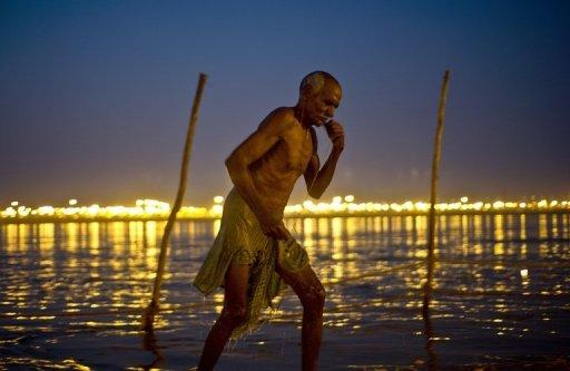 A devotee steps out after taking a holy dip during the Maha Kumbh Mela festival in Allahabad, India on February 9, 2013