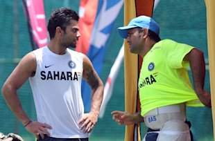 Indian cricketer Virat Kohli (L) speaks with team captain Mahendra Singh Dhoni.