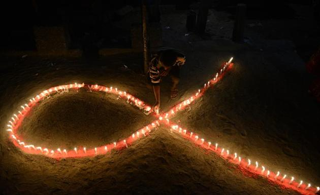 Indian volunteers and members of the West Bengal Voluntary Health Association (WBVHA) light candles in the shape of a red ribbon during the closing ceremony of an AIDS awareness campaign in Siliguri o