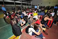 Hundreds of Taiwanese and mainland Chinese rounded up by Philippine police on suspicion of being involved in a major telephone scam wait to be processed by authorities at a police station in Canlubang, south of Manila, on August 23. The gang would pose as police and government prosecutors, telling their victims they had legal problems and would have to transfer money to a certain account