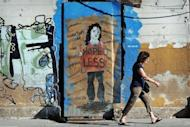 A woman walks by graffiti on a wall in Athens on June 14. World markets cast Spain back to the centre of the eurozone debt storm Monday, pushing its borrowing rate to a euro-era record and dashing hopes for a respite after Greek elections