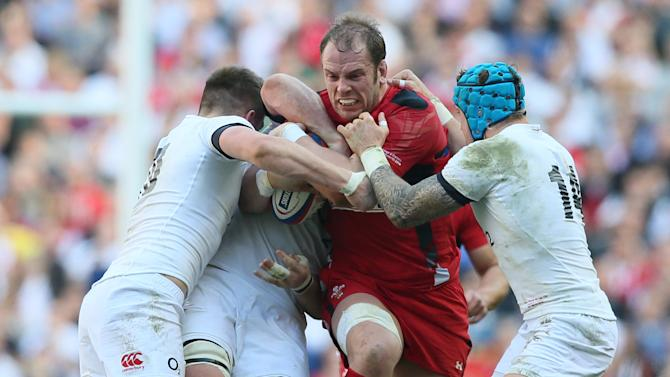Wales's Alun Wyn Jones, center, is tackled by England's Jack Nowell, right, and Danny Care during the Six Nations Rugby Union match between England and Wales at Twickenham stadium in London Sunday, March, 9, 2014. (AP Photo/Alastair Grant)