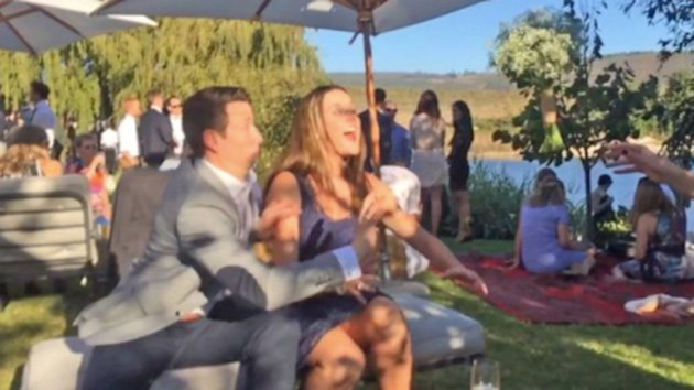 This guy moves to knock the bouquet out of his girlfriend's reach, and she appears none too thrilled.