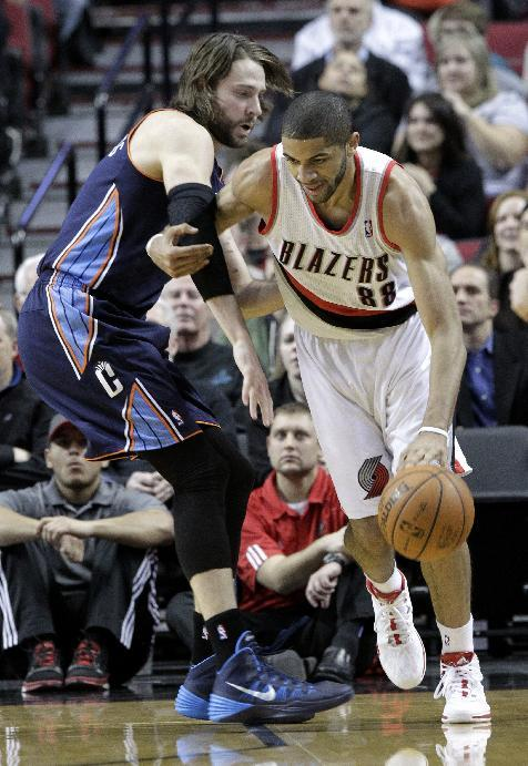 Portland Trail Blazers forward Nicolas Batum, right, from France, drives on Charlotte Bobcats forward Josh McRoberts  during the first half of an NBA basketball game in Portland, Ore., Thursday, Jan. 2, 2014
