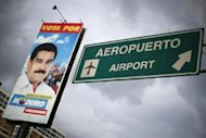 A road sign indicates the way to the Simon Bolivar international Airport next to a campaign billboard of Venezuelan President Nicolas Maduro in La Guaira, outside Caracas July 10, 2013. REUTERS/Jorge Silva