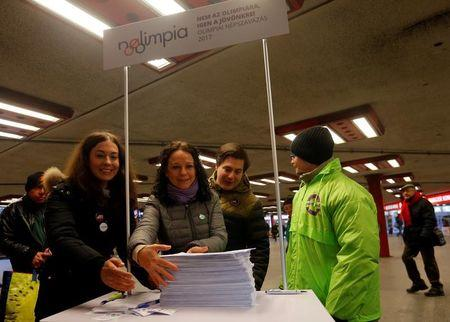 Szabo, co-chair of opposition party Parbeszed Magyarorszagert hands over documents with signatures supporting a referendum on Budapest's 2024 Olympic bid to political movement  Momentum at a stand in Budapest