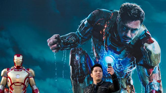 """FILE - In this April 6, 2013 file photo, a Chinese man uses a smartphone to take his own photo with an """"Iron Man"""" poster together with a costumed figure, left, during a promotional event of the new movie """"Iron Man 3"""" at the Imperial Ancestral Temple in Beijing's Forbidden City. From demanding changes in plot lines that denigrate the Chinese leadership, to dampening lurid depictions of sex and violence, Beijing is having increasing success in pressuring Hollywood into deleting movie content Beijing finds objectionable. It's even getting American studios to sanction alternative versions of films specially tailored for Chinese audiences, like """"Iron Man 3,"""" which debuts in theaters around the world later this week. The Chinese version features local heartthrob Fan Bingbing - absent from the version showing abroad - and lengthy clips of Chinese scenery that local audiences love. (AP Photo/Andy Wong, File)"""
