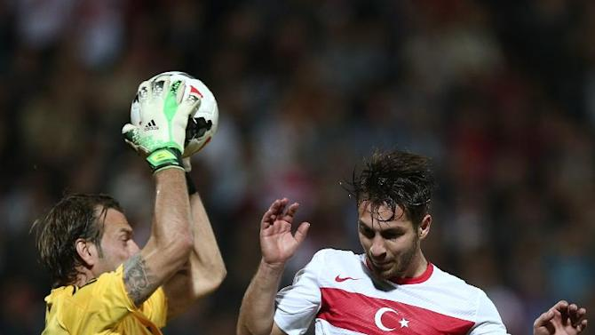 Turkey's Adem Buyuk, right, is blocked by goalkeeper Roy Carroll of Northern Ireland during their friendly soccer match in Adana, Turkey,  Friday, Nov. 15, 2013.(AP Photo)