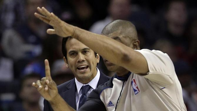 Miami Heat coach Erik Spoelstra, back, is called for a technical foul by an official during the second half of an NBA basketball game against the Charlotte Bobcats in Charlotte, N.C., Saturday, Nov. 16, 2013. Miami won 97-81