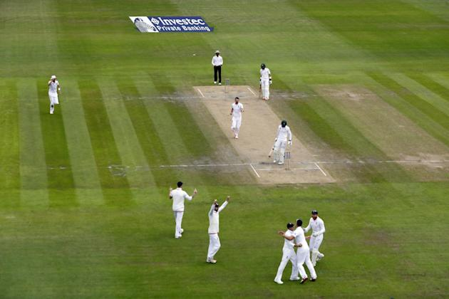 England's James Anderson and Joe Root celebrate taking the wicket of Pakistan's Shan Masood with teammates
