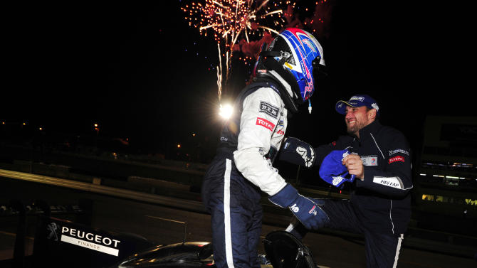 Peugeot driver Franck Montagny, right, of France, congratulates his teammate Stephane Sarrazin, also of France, after winning the American Le Mans Series' Petit Le Mans auto race at Road Atlanta, Saturday, Oct. 1, 2011, in Braselton, Ga.  (AP Photo/Rainier Ehrhardt)