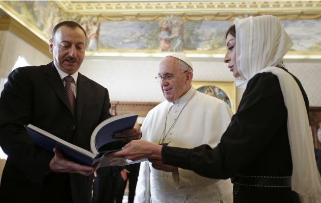 Pope Francis receives a gift from President of Azerbaijan Aliyev and his wife Aliyeva during a meeting at the Vatican