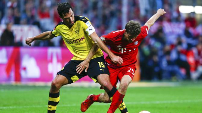 Bayern Munich's Mueller fights for the ball with Borussia Dortmund's Hummels during their German first division Bundesliga soccer match in Munich