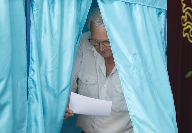 A man looks at his ballot inside a voting booth during a snap presidential election in the village of Tuzdybastau