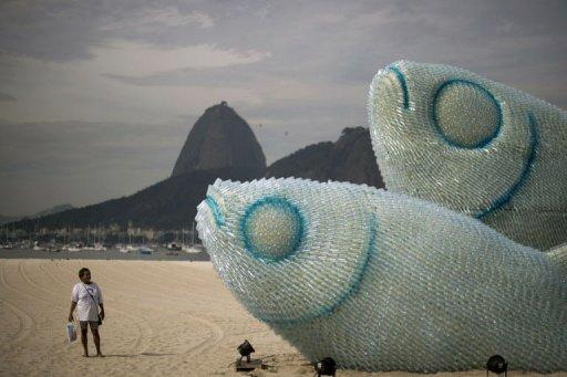 A woman looks at an installation made of recycled plastic bottles representing fishes