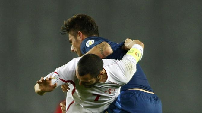 Georgia's Jaba Kankava fights for the ball with France's Olivier Giroud during their 2014 World Cup qualifying soccer match at the Boris Paichadze National Stadium in Tbilisi