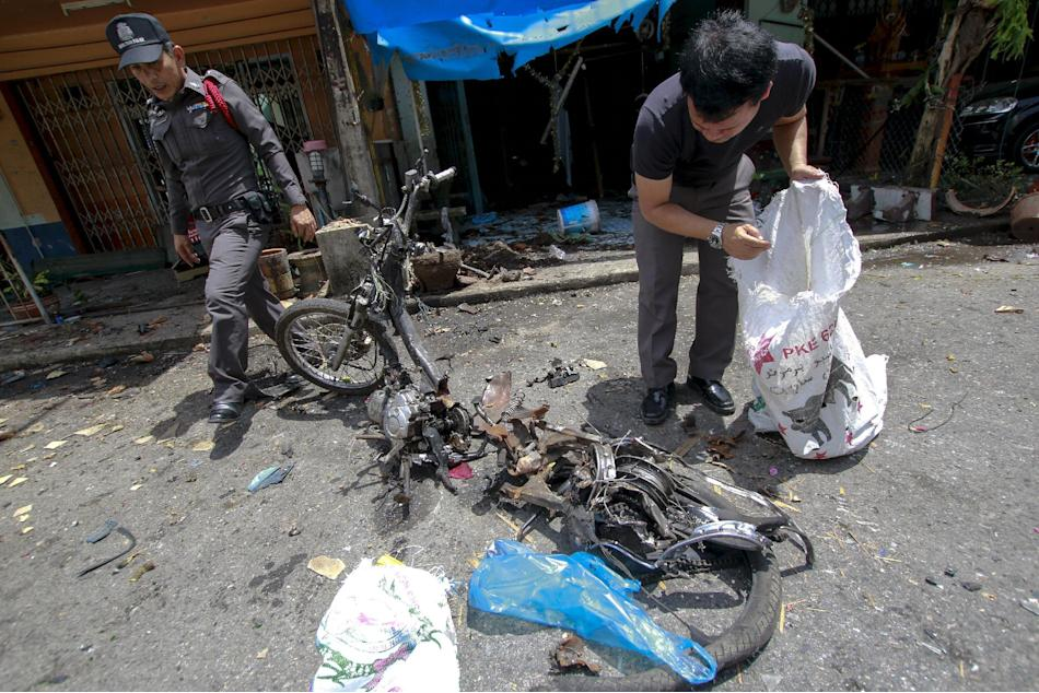 Police and forensic experts inspect the site of a motorcycle bomb attack at Padang besar district in the troubled southern province of Songkha