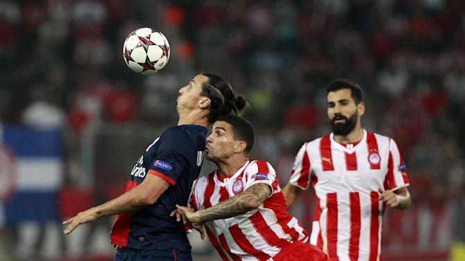 Paris Germain's Zlatan Ibrahimovic, left, and Olympiakos'  Carl Medjani, center, fight for the ball, during the soccer Champions League group C match between Olympiakos and Paris Saint Germain in Piraeus, Greece, Tuesday, Sept. 17, 2013