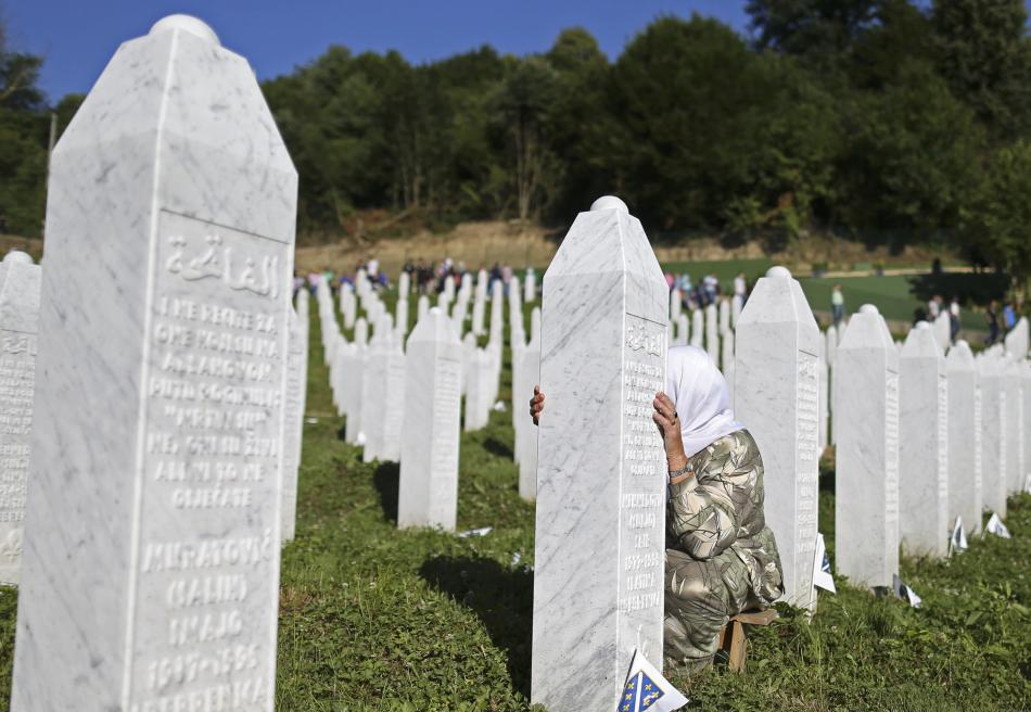 A woman mourns at a grave in Memorial Center Potocari, near Srebenica