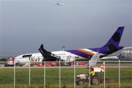 An airplane takes off in the distance as airport staff work around a Thai Airways plane that skidded off the runaway while landing at Bangkok's Suvarnabhumi Airport September 9, 2013. REUTERS/Athit Perawongmetha