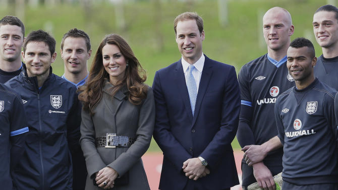 Prince William and Kate, Duchess of Cambridge stand with members of the England football squad at St George's Park near Burton Upon Trent in Staffordshire, England,Tuesday, Oct. 9, 2012. Britain's Duke and Duchess of Cambridge visited the new national training facility for England's football teams, to officially open the 330 acre site which includes indoor and outdoor training pitches, a hotel, conference centre, medical facilities, health club and spa. (AP Photo/Kirsty Wigglesworth)