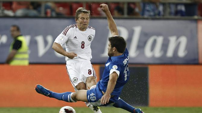 Latvia's Aleksandrs Cauna, left, is tackled by Greece's Sokratis Papastathopoulos during their World Cup Group G qualifying soccer match at the Karaiskaki stadium in Piraeus port, near Athens, on Tuesday, Sept. 10, 2013