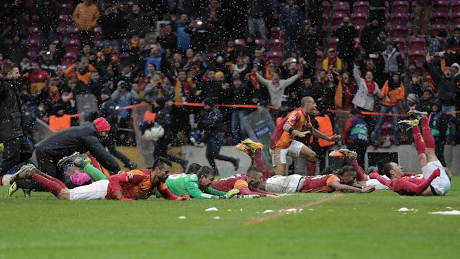 Galatasaray's players celebrate after their Champions League soccer match victory over Juventus at the TT Arena Stadium in Istanbul, Turkey, Wednesday, Dec. 11, 2013. The match was halted Tuesday in the 31st minute with the score at 0-0 as hail and snow began to fall heavily in Istanbul, but resumed Wednesday. (AP Photo)