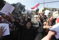"Egyptian women supporting the army hold booklets of Egyptian constitution drafts saying ""Yes"", and dance as they hold pictures of army chief General Abdel Fattah al-Sisi, beside a polling station in Cairo, January 15, 2014. REUTERS/Mohamed Abd El Ghany"