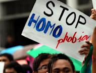 A student hoists an anti-homophobia placard during a rally at the University of the Philippines in the town of Los Banos, Laguna province, south of Manila on July 19. Gay sex in a conservative Catholic society where the influential church forbids the use of condoms is fuelling an alarming rise of HIV infections in the Philippines, experts warn