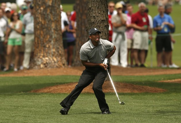 Tiger Woods of the U.S. watches his approach shot to the seventh green during first round play in the 2013 Masters golf tournament in Augusta