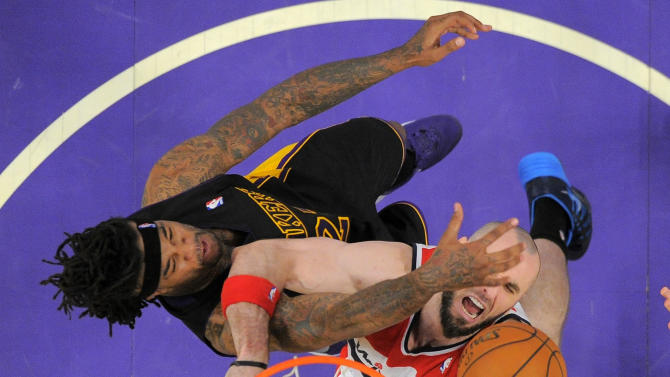 Washington Wizards center Marcin Gortat, of Poland,, right, puts up a shot as forward Jordan Hill defends during the second half of an NBA basketball game, Friday, March 21, 2014, in Los Angeles. The Wizards won 117-107