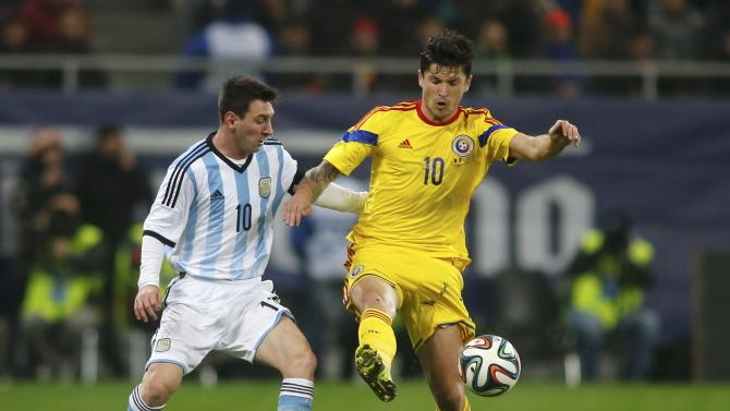 Romania's Tanase challenges Argentina's Messi during their international friendly soccer match at the National Arena in Bucharest