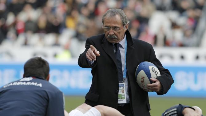 Italy's coach Jacques Brunel speaks to his team before the start of their Six Nations rugby union match against France at the Stade de France in Saint-Denis