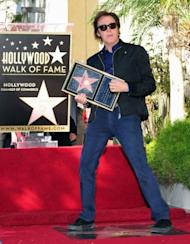 Music legend Paul McCartney mimicks playing his bass guitar while steeping on his just unveiled star on the Hollywood Walk of Fame