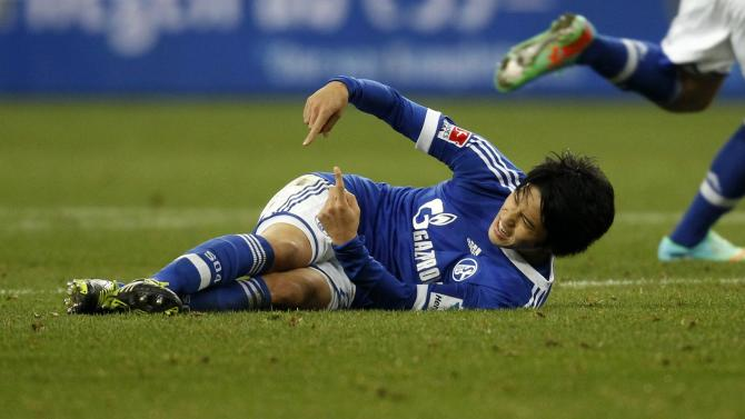 Schalke 04's Uchida lies on the field after an injury during the German first division Bundesliga soccer match against Hanover in Gelsenkirchen