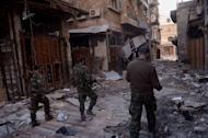 Syrian government forces walk through the old souk in the northern Syrian city of Aleppo on January 3, 2012, after they allegedly recaptured the area from opposition forces. At least nine people were killed when a car bomb exploded in the Syrian capital Damascus, the Syrian Observatory for Human Rights said early Friday