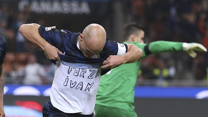 "Inter Milan Argentine midfielder Esteban Cambiasso celebrates after scoring during the Serie A soccer match between Inter Milan and Hellas Verona at the San Siro stadium in Milan, Italy, Saturday, Oct. 26, 2013. The writing on the shirt ""Forza Ivan"" (Go Ivan) is a get well wish for his teammate Ivan Cordoba, recently hospitalized"