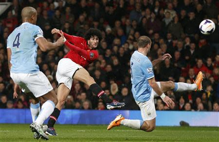 Manchester United's Fellaini shoots past Manchester City's Zabaleta during their English Premier League soccer match in Manchester