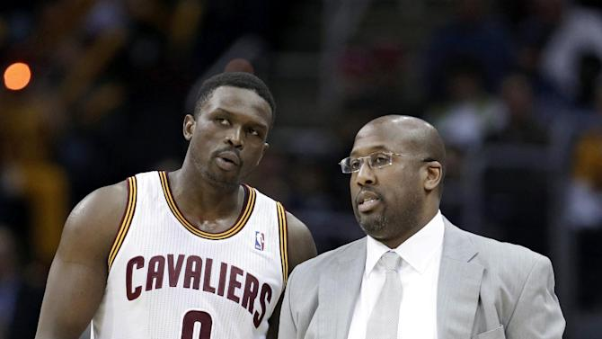 Cleveland Cavaliers head coach Mike Brown, right, talks with Luol Deng during the third quarter of an NBA basketball game, Monday, Jan. 20, 2014, in Cleveland. Dallas defeated Cleveland 102-97