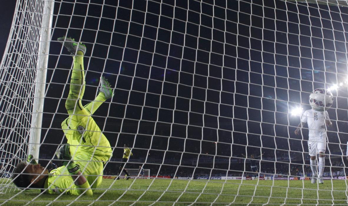 Uruguay's goalie Muslera tumbles in the net after allowing in a goal by Argentina's Aguero during their first round Copa America 2015 soccer...