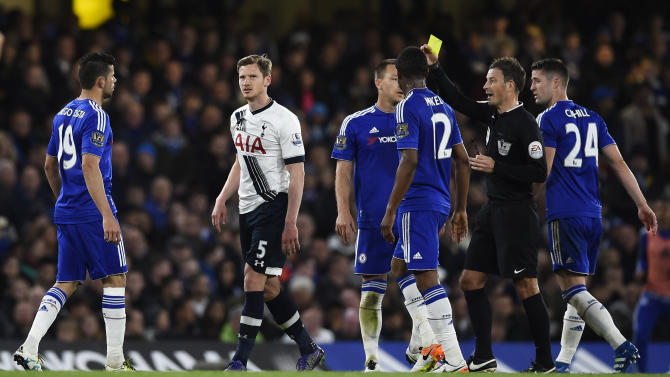 Referee Mark Clattenburg shows a yellow card