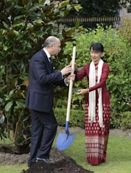 France's Foreign Minister Laurent Fabius (L) gives a shovel to Myanmar pro-democracy leader Aung San Suu Kyi to plant the tree of Freedom in the garden of the Foreign Affairs Ministry in Paris. Myanmar's democracy champion Aung San Suu Kyi, nearing the end of her triumphant Europe tour in France, accepted another award Wednesday as she became an honorary citizen of Paris