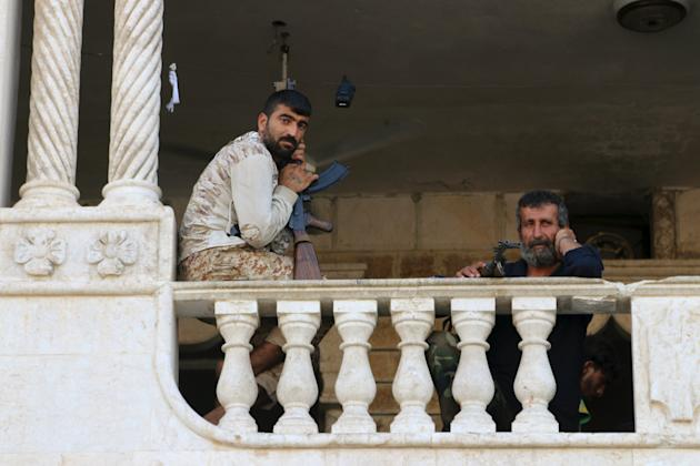 Free Syrian Army fighters, part of the Suqour al-Jabal (Mountain Hawks) brigade, rest with their weapons at their headquarters building in Aleppo