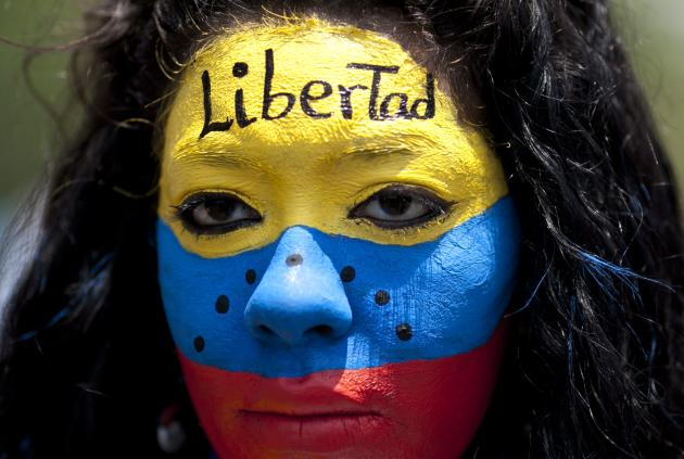 """An opposition demonstrator, her face painted with the colors of the Venezuelan national flag and the word """"Freedom"""" on her forehead, participates in the May Day march in Caracas, Venezuela,"""