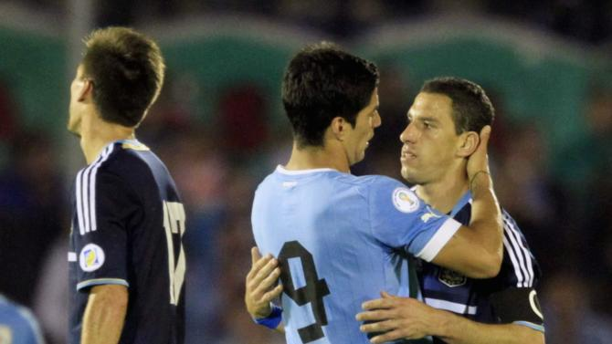 Argentina's Rodriguez is embraced by Uruguay's Suarez at the end of their 2014 World Cup qualifying soccer match in Montevideo