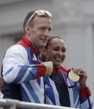 Britain's athletes Richard Whitehead, left, and Jessica Ennis, right, show their gold medals as the Team GB Olympic and Paralympic teams parade in the streets of London, Monday, Sept. 10, 2012. Our Greatest Team Parade, the procession of athletes, celebrates the achievements of British Olympians and Paralympians at the London 2012 Games. (AP Photo/Lefteris Pitarakis)