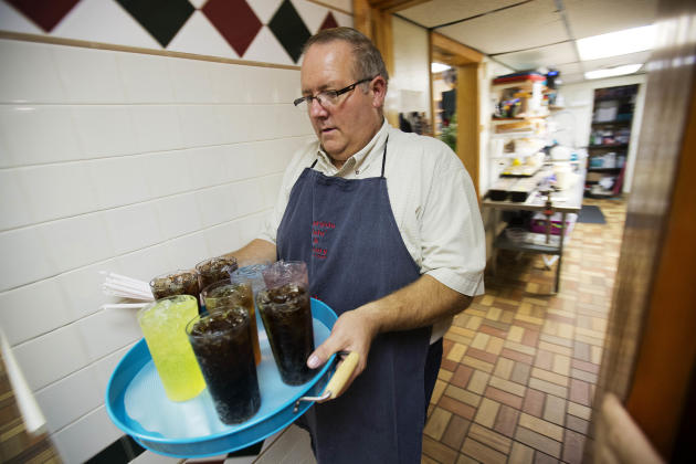 Mark Muncy carries drinks to customers at the Riverside Cafe and Bakery Monday, Oct. 5, 2015, in Welch, W.Va. Muncy worked in the coal industry for years before losing his job when the mine he worked