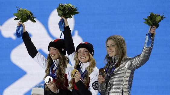 Canada's Justine Dufour-Lapointe, center, poses with her gold medal in the women's moguls freestyle skiing along side her sister silver medalist Chloe Dufour-Lapointe, left, and bronze medalist Hannah Kearney of the United States during their medals ceremony at the 2014 Winter Olympics, Sunday, Feb. 9, 2014, in Sochi, Russia
